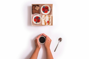 Creative photo of box with cakes and cup of coffee between female hands on white background. Top view