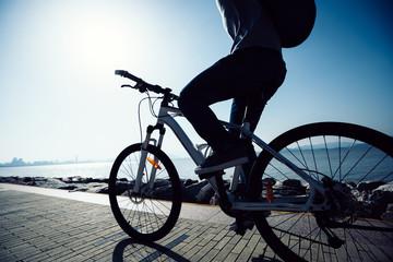 silhouette cyclist riding bike in the sunrise coast road