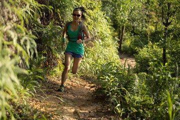 Determined woman trail runner running in morning forest