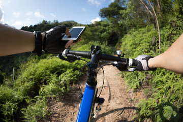 Riding on top of hill, holding mobile phone, using online application for searching GPS coordinates while riding bike in forest on sunny day  .