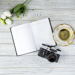 white ustom, diary, antique camera and cup of coffee and saucer on a light background, flat lay