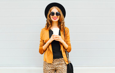 Elegant woman with coffee cup wearing retro elegant hat, sunglasses, brown jacket and black handbag over grey background