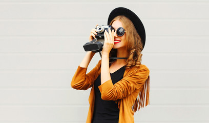 Pretty elegant cool girl with retro film camera wearing a elegant hat, brown jacket, in profile outdoors over city grey background