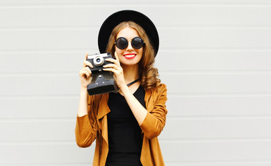 Happy cool young woman model with retro film camera wearing a elegant hat, brown jacket outdoors over city grey background