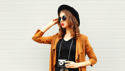 Elegant young girl model with retro film camera wearing elegant hat, brown jacket outdoors over city grey background