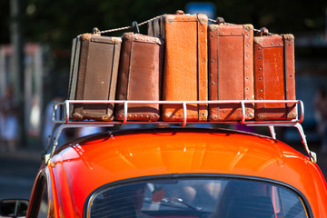 suitcases with things on the roof of the car