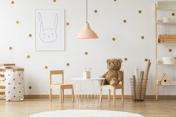 Teddy bear on wooden chair next to table in gold kid's room interior with lamp and poster. Real photo