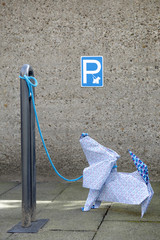 Origami dog in front of concrete wall, parking sign