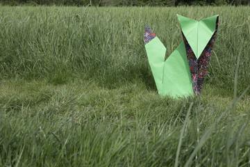 Origami fox sitting on meadow