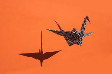 Origami crane, orange background, shadow, copy space