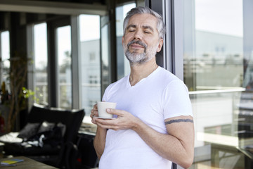 Man standing at French enjoying cup of coffee