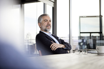 Confident businessman sitting at desk in office thinking