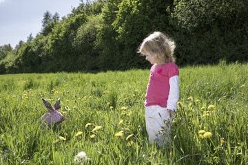 Little girl with origami rabbit on meadow