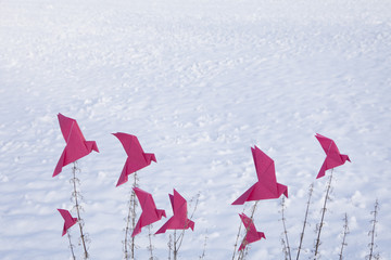 Origami birds sitting on grasses in winter