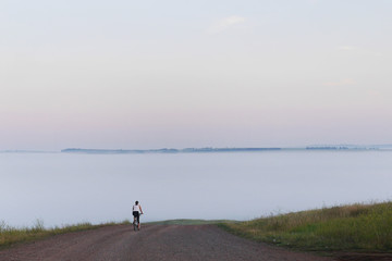 A dense fog on the field in the countryside. A woman is riding a bicycle on the road in the distance. A minimalistic photo.