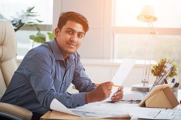 Side view of cheerful Indian man holding papers in office and looking at camera in backlit
