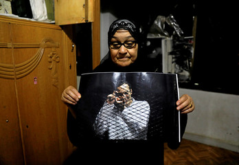 "Reda Mahrous, the mother of jailed Egyptian photojournalist Mahmoud Abu Zeid, also known as ""Shawkan"", poses with a photo in his room, ahead of his verdict next Saturday, in Cairo"