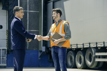 Worker shaking hands with businessman