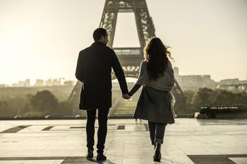 Couple walking towards Eiffel Tower