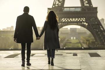 Couple holding hands near Eiffel Tower