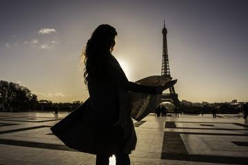 Woman reading map near Eiffel Tower