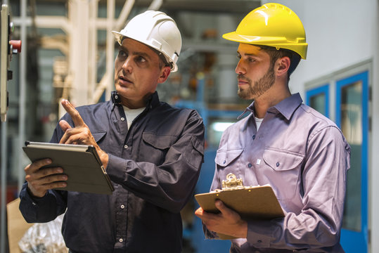 Factory workers examining control panel in factory