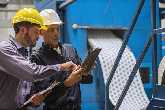 Factory workers using digital tablet in factory