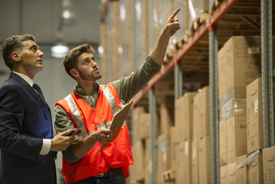 Worker and businessman with digital tablet and clipboard in warehouse