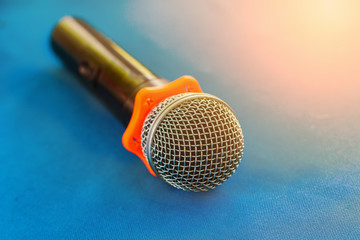 Wireless microphone for singing , talk, and broadcast on a blue table.