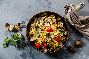 Pasta Spaghetti alle Vongole Seafood pasta with Clams in frying cooking pan on concrete background