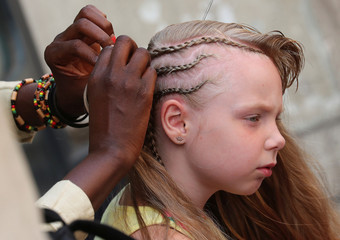A street hairstylist makes braids to a girl in central Rome