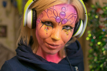 A woman with a painted face wearing headphones.