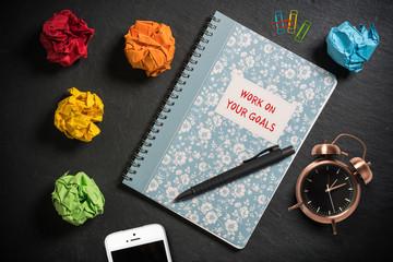 """Notizbuch mit Aufschrift """"Work on your goals"""" auf Schieferplatte mit Büroutensilien"""