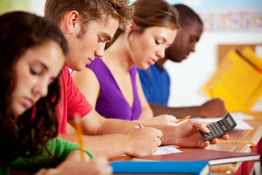Students: Smart Male Teen Using Calculator For Homework