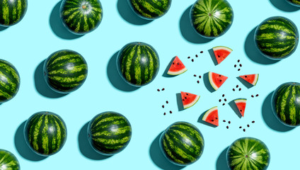 Whole and sliced watermelons on a blue background