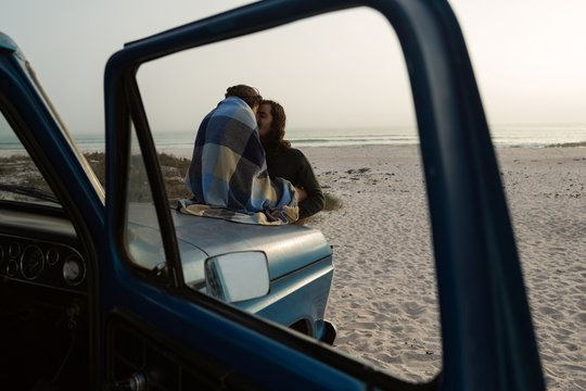 Young couple romancing on pickup truck bonnet