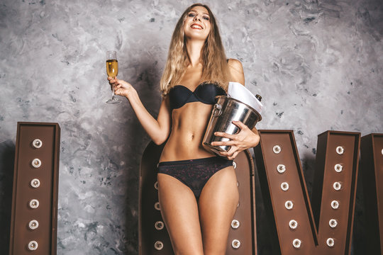 Pretty lady with big attractive ass smiling and holding a bottle and a glass with expensive champagne. Elegant model in fashionable lingerie. Concept of fun at ease on vacation
