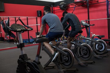Athletes exercising on exercise bikes in a gym