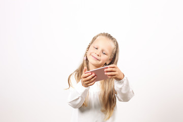 Portrait of positive & funny four year old blonde little girl, holding mobile cell phone, smiling at camera, taking selfies. Childhood & technology concept. Isolated background, copy space, close up.