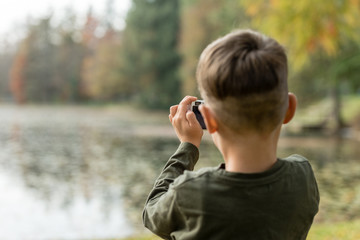 Young boy photographing a lake outdoors