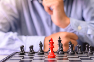 Man thinging to play  a chess game, moving the pawn one field forward. Concept of business strategy and tactic.