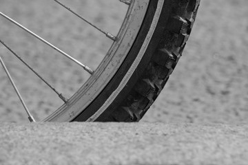 Monochrome photo of a bicycle wheel is close