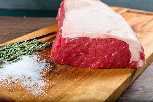 Raw whole beef sirloin on chopping board