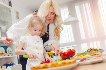 Mother teaches daughter to cut peppers, concept of cooking.