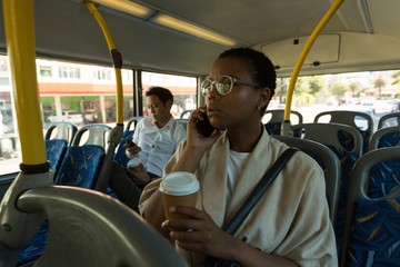 Woman talking on mobile phone while having coffee