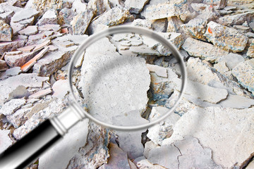 Looking for danger asbestos particles in industrial waste after demolishing a concrete wall - Concept image seen through a magnifying glass