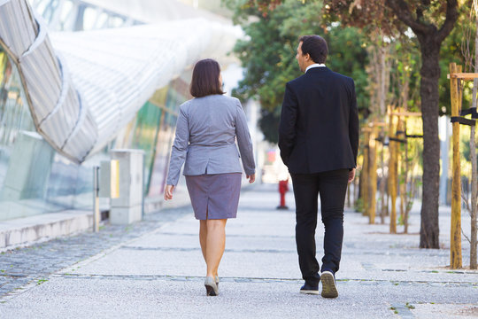 Confident business colleagues in formal suits going to office over city street. Modern employees walking during break. Business people strolling at noon concept