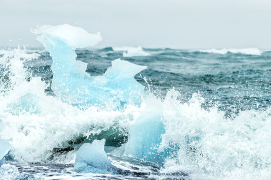 Waves crashing on Jokulsarlon Diamond Ice glacial beach in Iceland against glacier icebergs, splashing water on Atlantic ocean shore during raining, rain storm