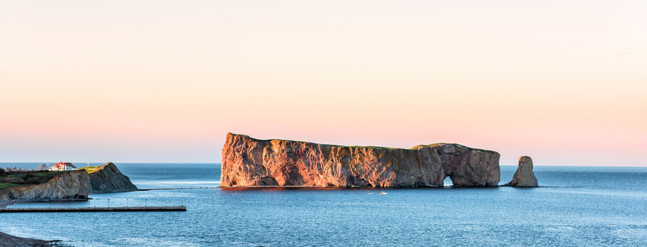 Famous large Rocher Perce rock in Gaspe Peninsula, Quebec, Gaspesie region, Canada at sunset, Saint Lawrence gulf, boat, ship, houses, wharf, dock, pier
