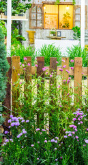 Beautiful cozy home flower garden on summer./ White wood fence and flower decoration in cozy home garden on summer.